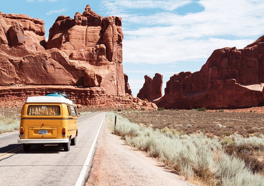 Van on a road surrounded by Canyons