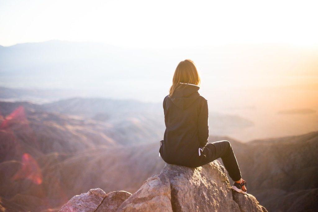 Woman sitting near a cliff